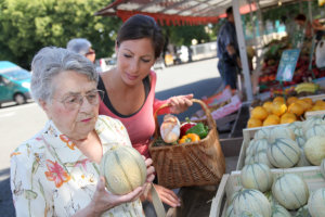 caregiver assisting old woman to buy vegetables