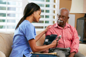 caregiver monitoring the blood pressure of the old woman