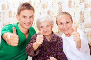 two caregivers and old woman posing thumbs up